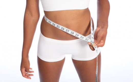 10389749 - healthy torso of young african american woman wearing white sports underwear, checking diet weight loss on waist with tape measure, standing against white background.